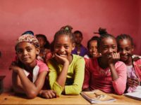 A group of girls sit in a classroom with a pink wall behind them.
