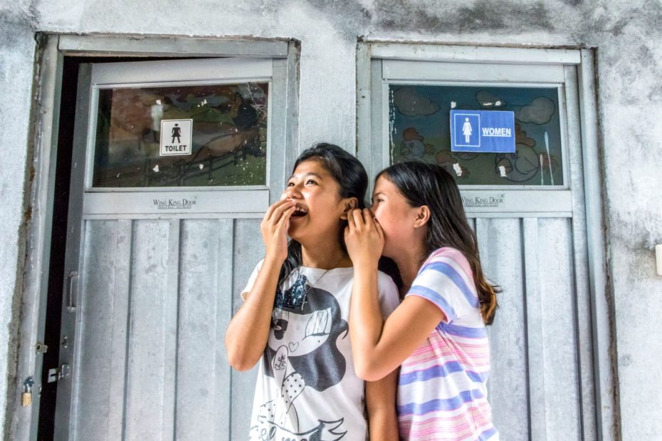 Two girls stand outside a bathroom, giggling.