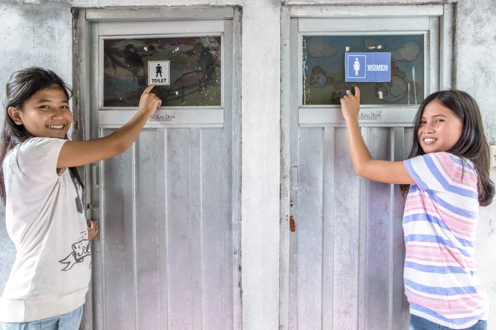 "Two girls stand outside bathrooms, pointing at the ""women's"" signs."