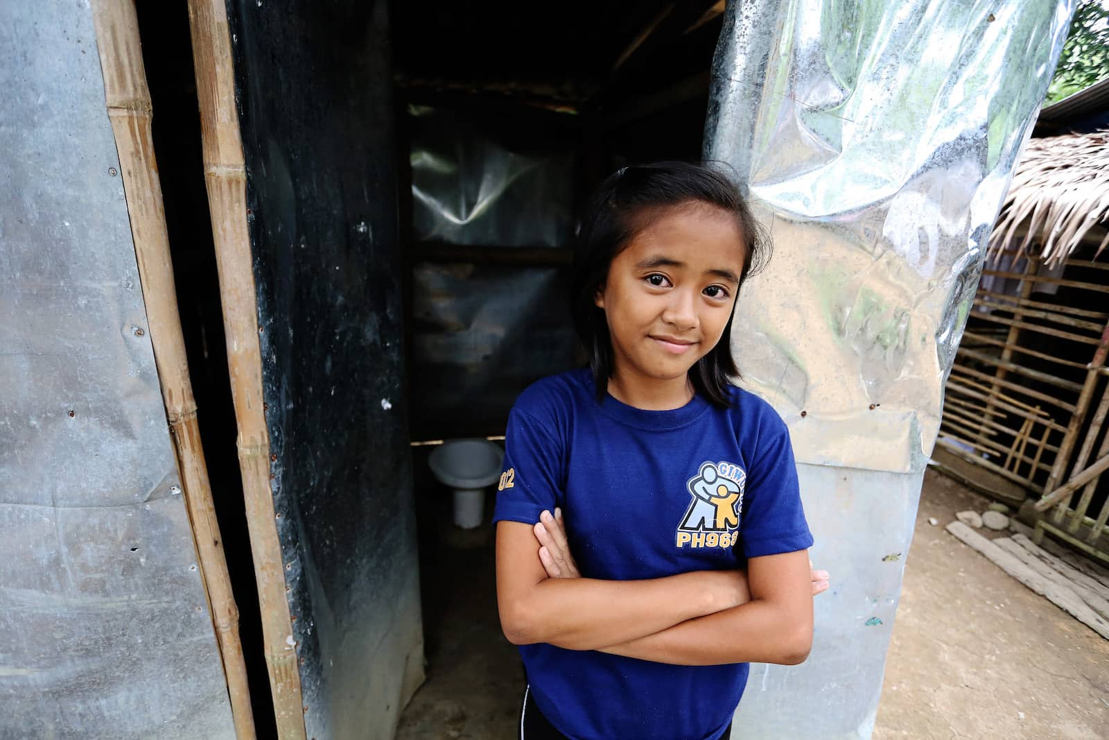 The History of the Toilet: A girl stands in front of a silver sheet building with a toilet inside.