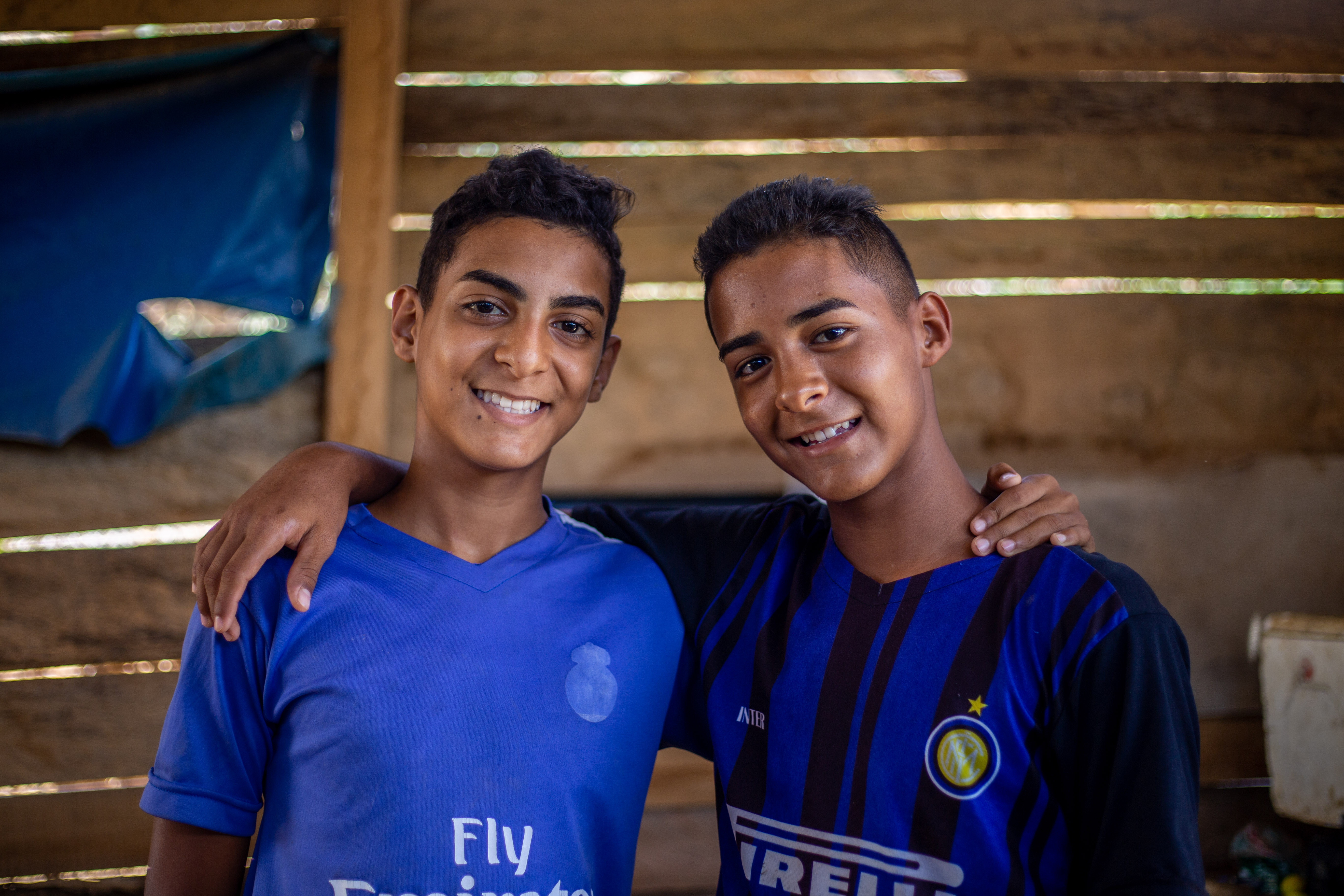 Two teen boys wearing blue and black shirts have their arms around each other, smiling at the camera.