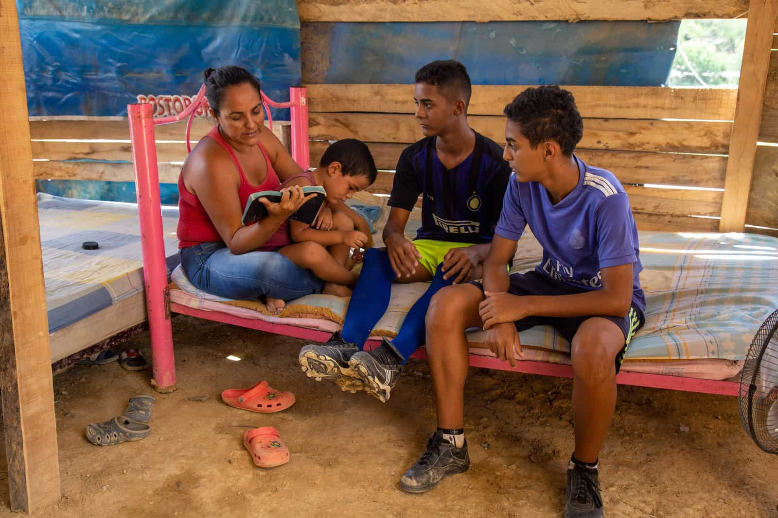 A woman and three boys sit on a bed reading the Bible, in a house with wooden slat walls and dirt floors.