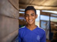 A teen boy in a blue shirt smiles at the camera inside a wooden house.