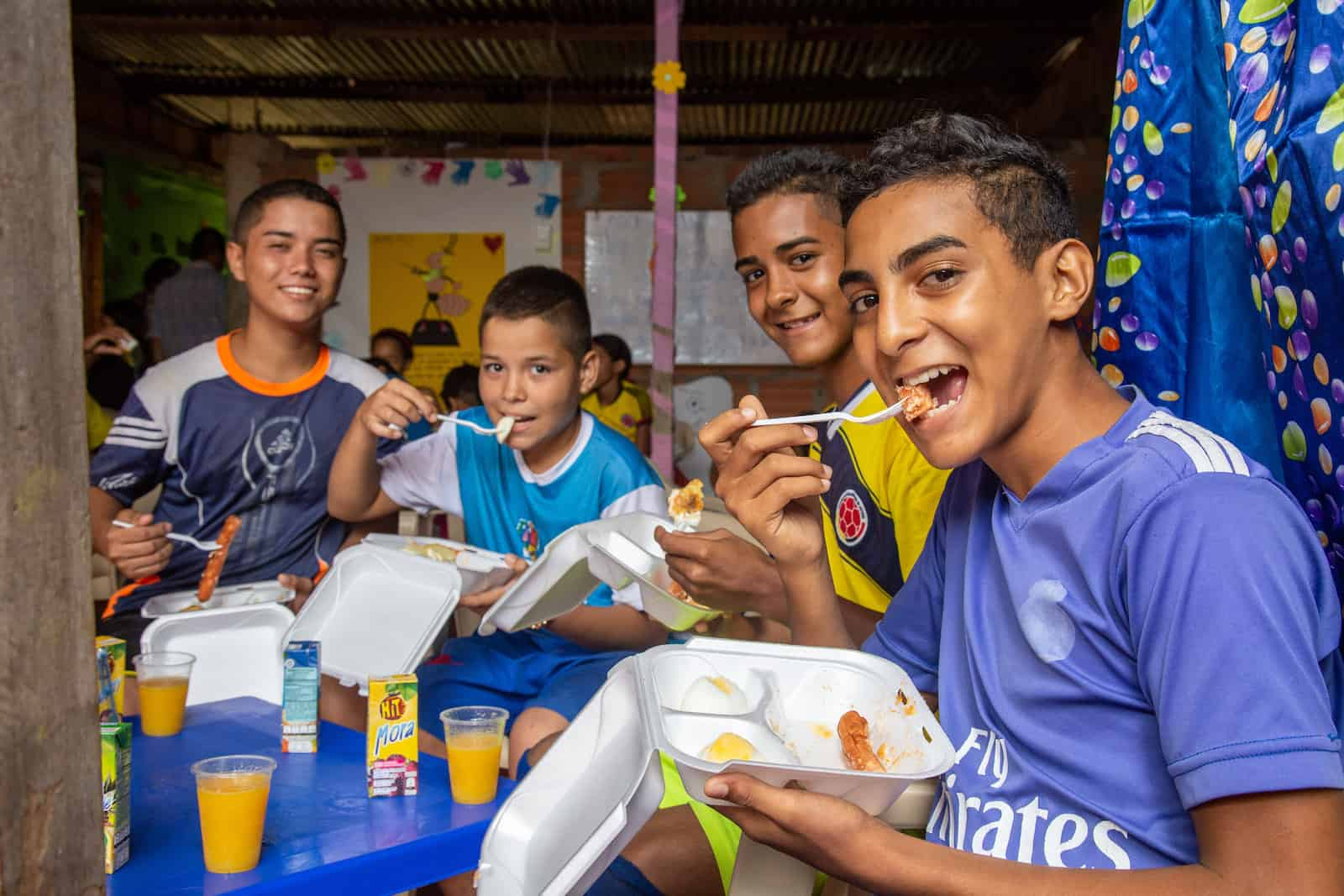 Boys sit around a table eating food out of styrofoam containers, smiling at the camera.