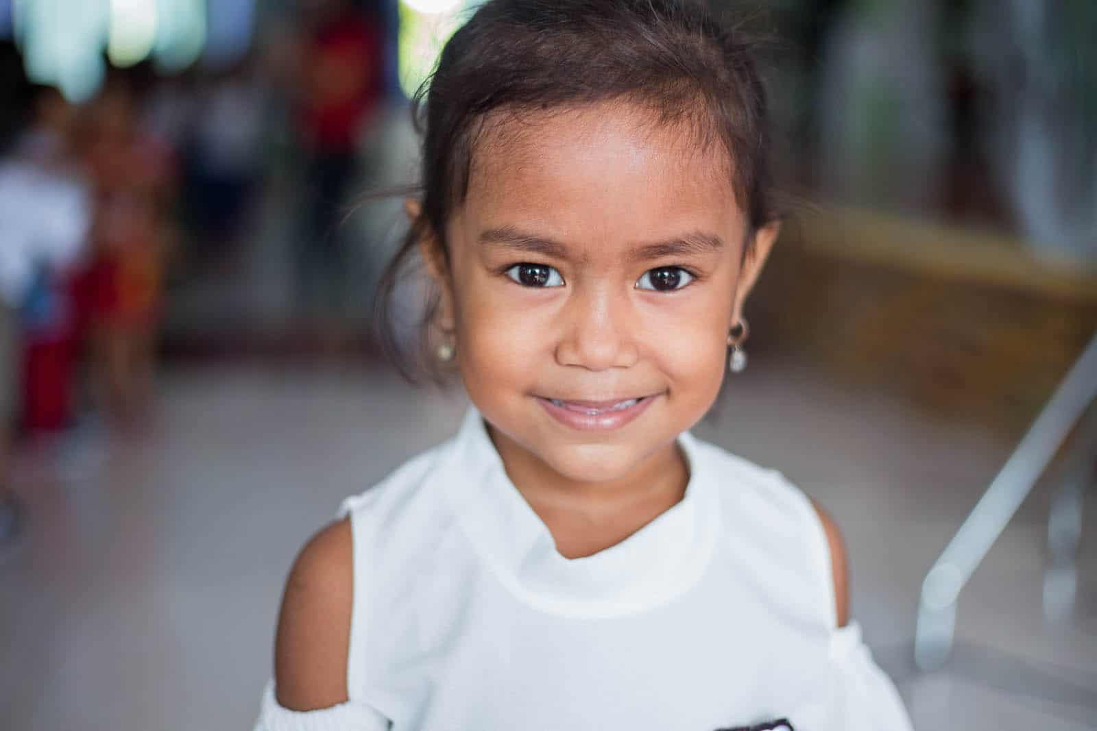 Convention on the Rights of the Child: A girl in a white shirt smiles at the camera.