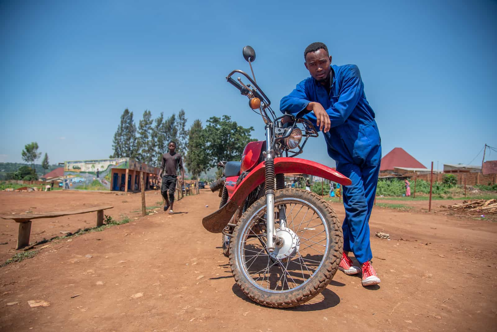 A young man in a blue jumpsuit stands next to a red motorcycle.