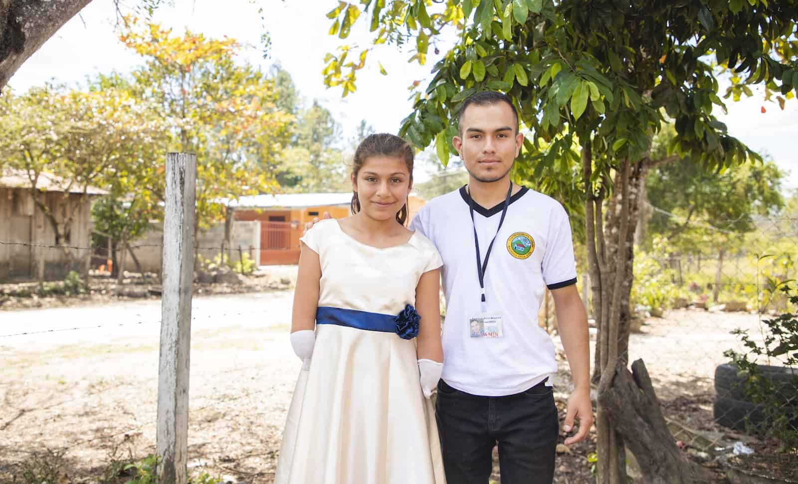A young man and a girl with limb difference stand outside in front of a tree.