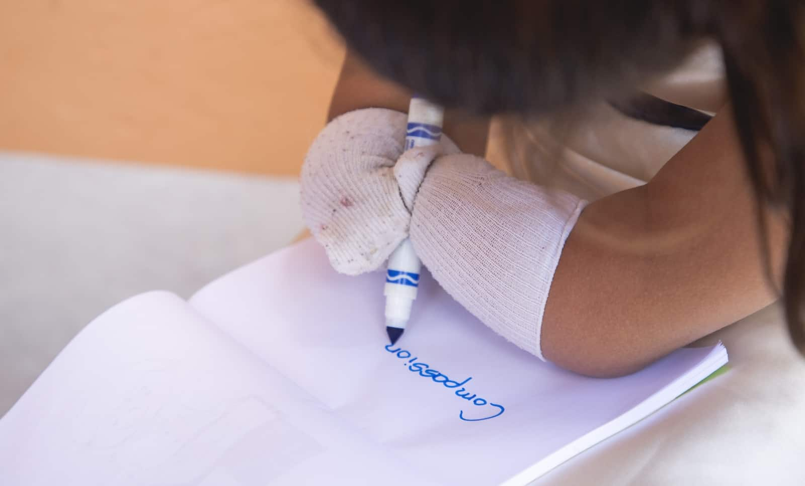 "A girl with limb difference writes the word ""Compassion"" on a notepad."