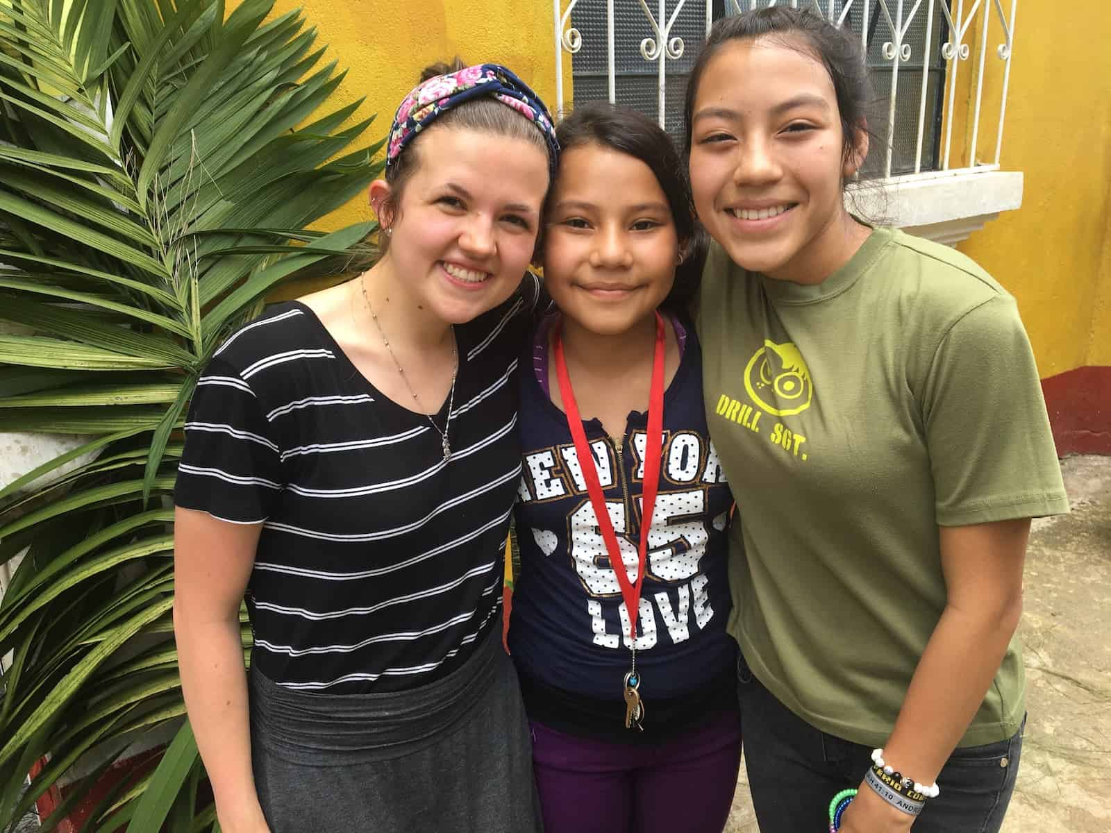 A young woman poses with two Guatemalan girls