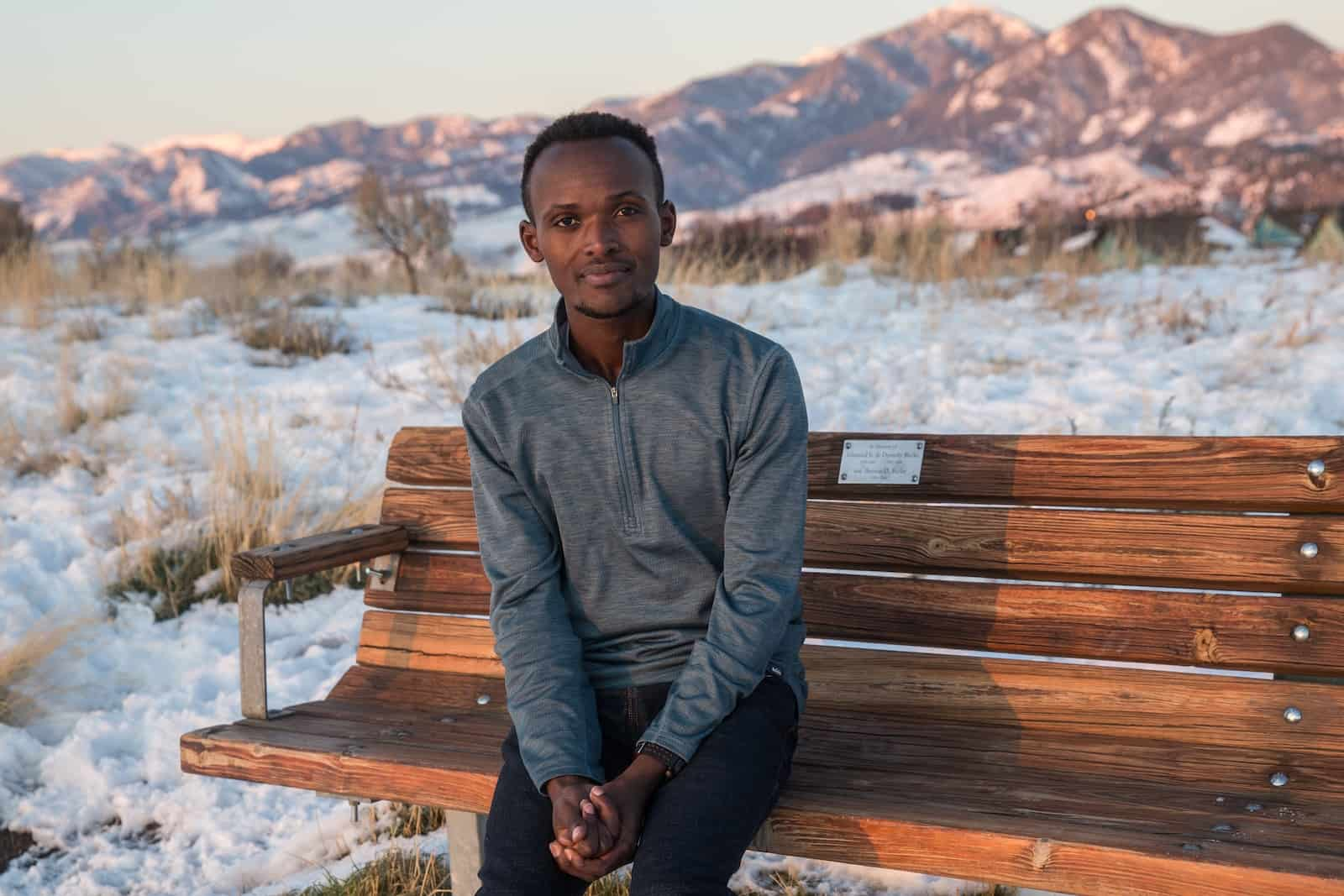 A man in a grey sweater sits on a bench in front of snowy hills.