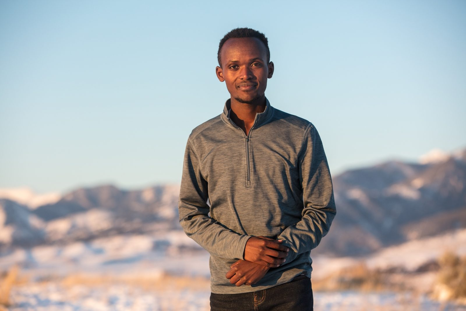 A man stands in a gray shirt in front of snowy hills, smiling at the camera.