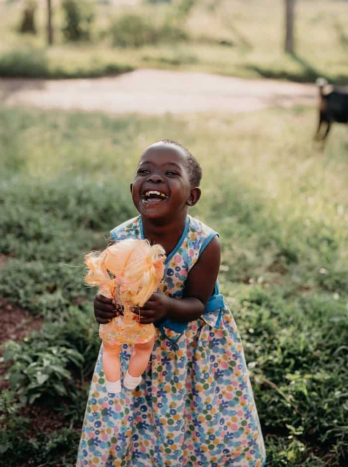 A girl who received a charity gift of heart surgery in a blue floral dress holds a doll and laughs.