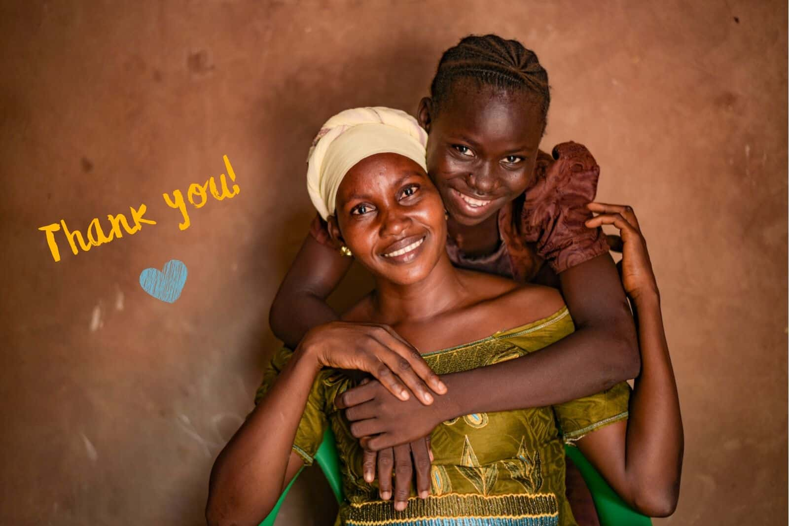 "A girl in a brown dress puts her arms around a woman in a green dress and yellow turban, smiling. Text: ""Thank You!"""