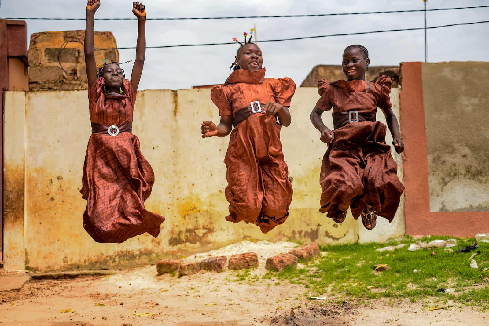 Three girls wearing brown dresses jump in the air, smiling.