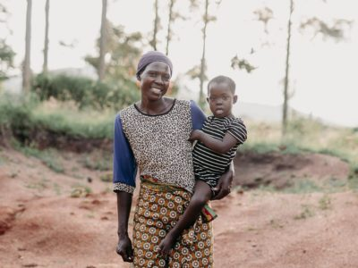 A woman holds a girl on her hip, standing on a dirt road.