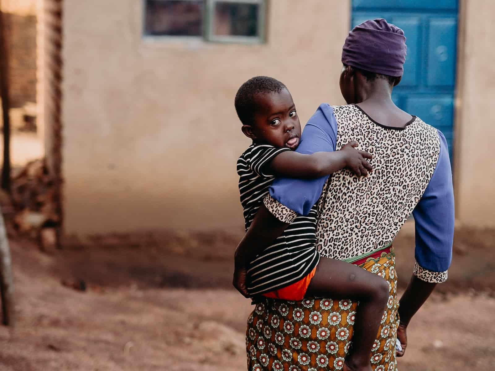 A woman walking towards a house holds a child in her arms.
