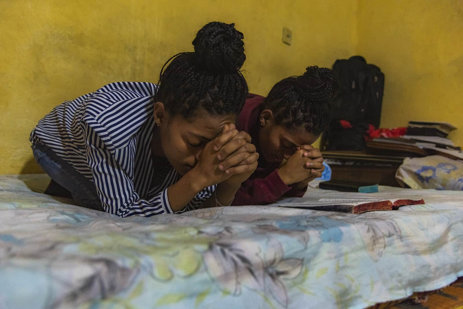Two girls kneel on a bed, praying.