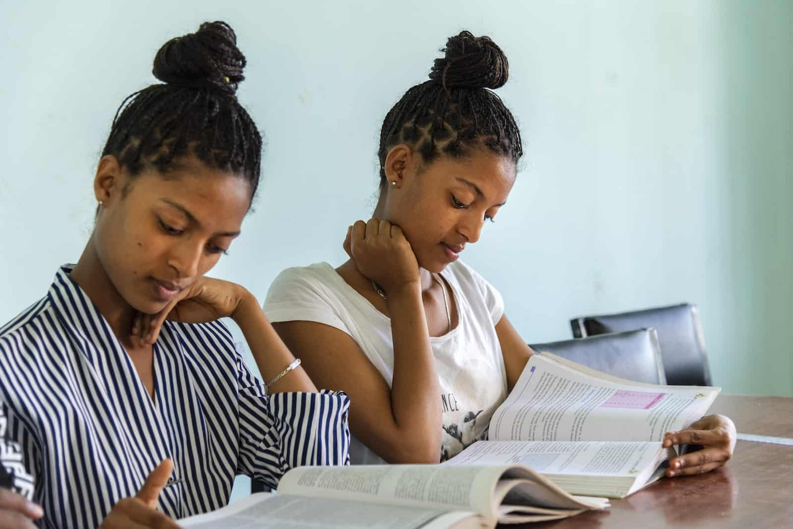 Two teenage girls sit at a desk, reading.