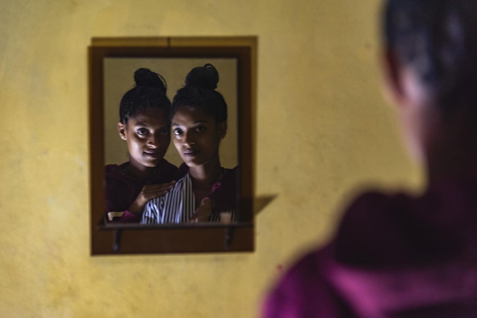 An orphan story: The mirror reflection of two teenage girls looking in the mirror.