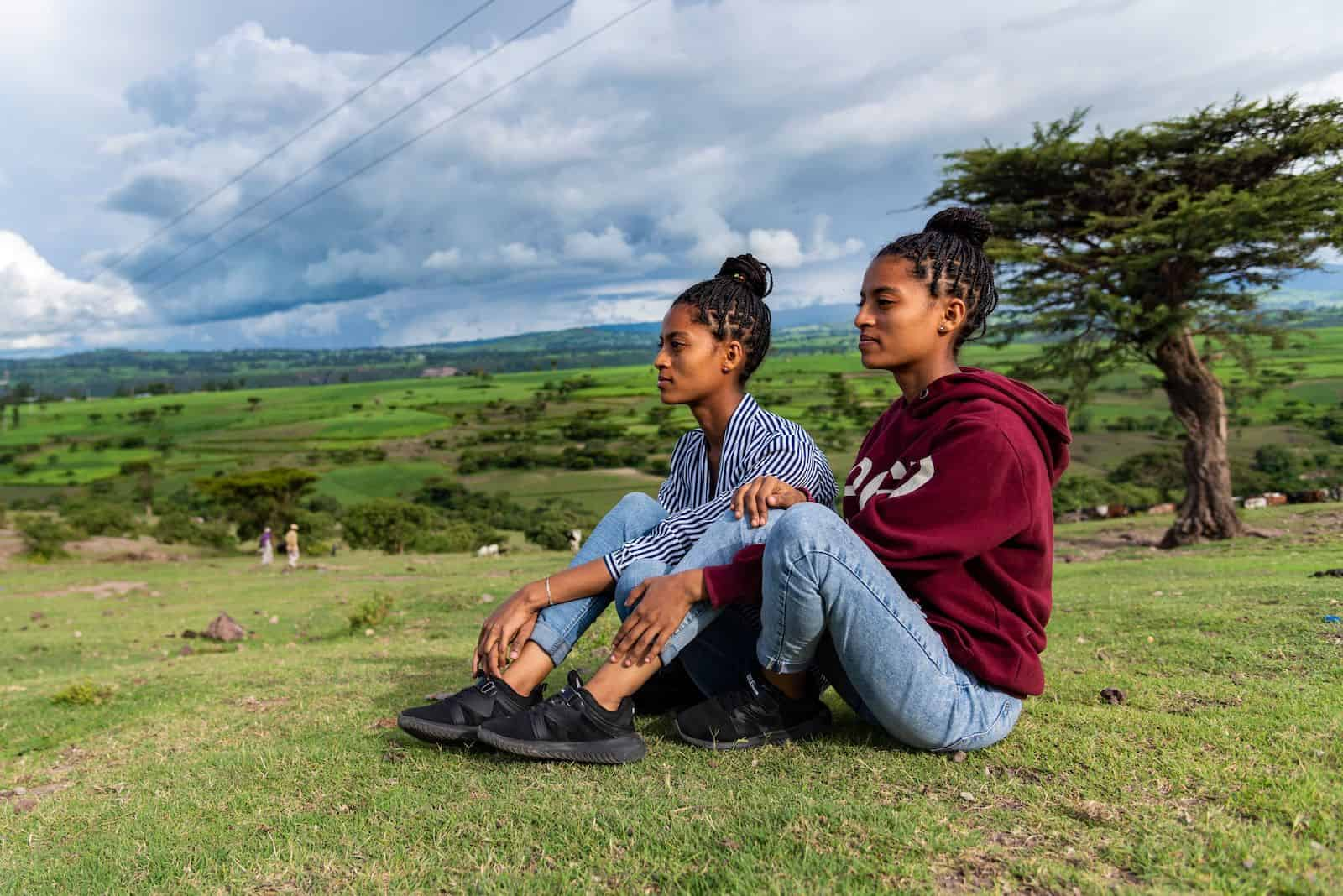 An orphan story: Two teenage girls sit on a hill and look to the distance.