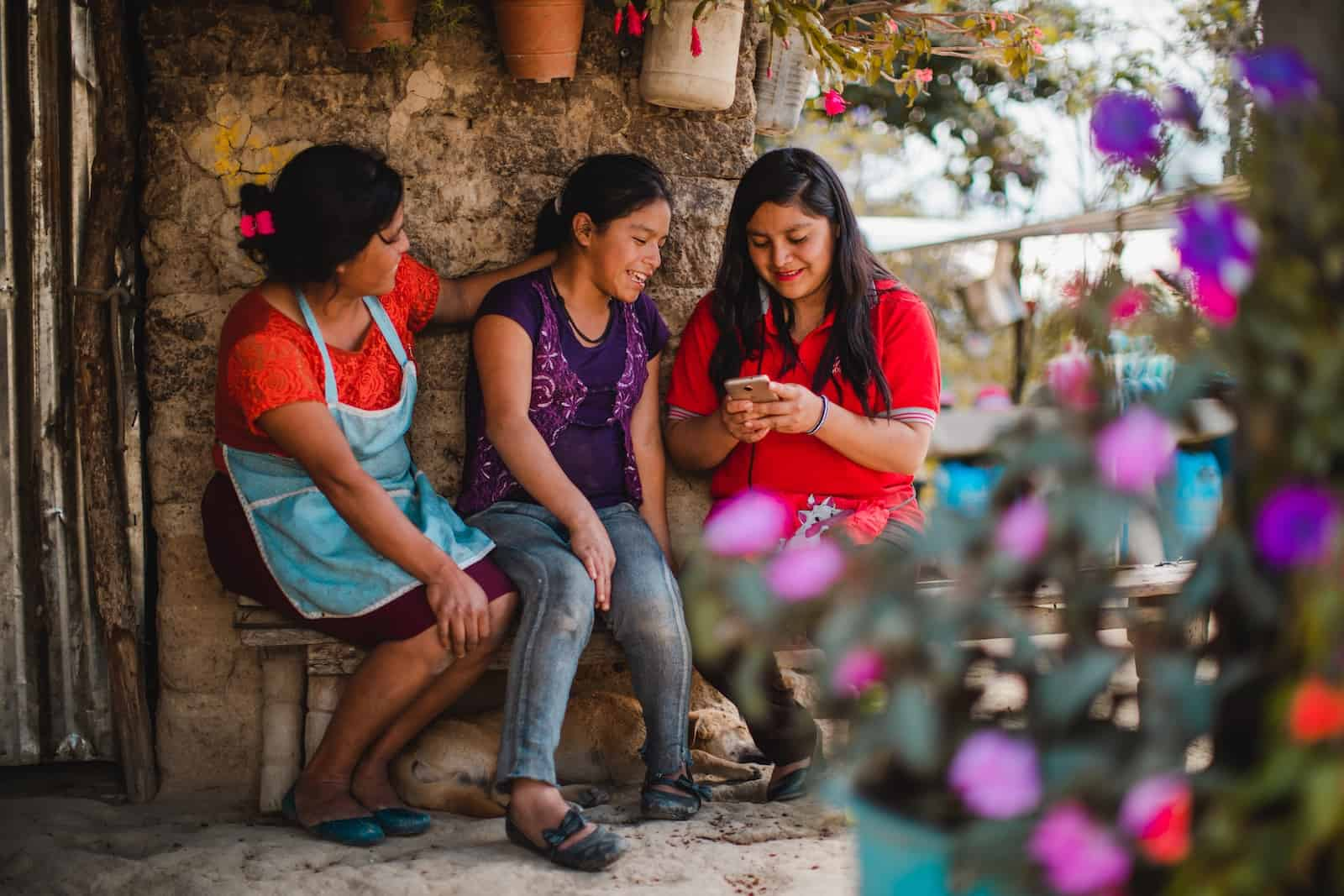 Two women and a girl sit outside on a bench, looking at a cell phone using technology for poverty reduction.