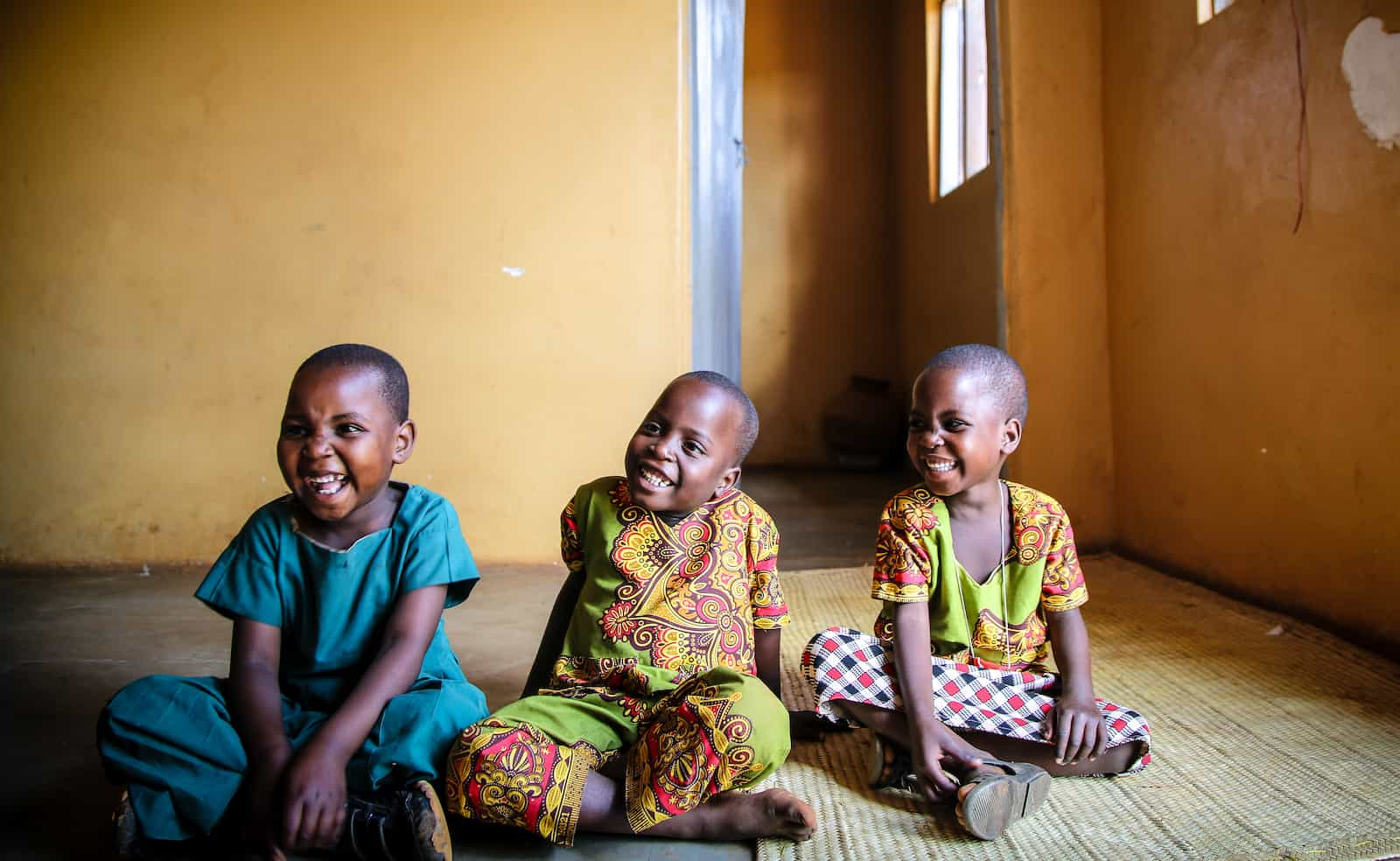 Three young children in bright colored clothes sit on the floor inside a home.