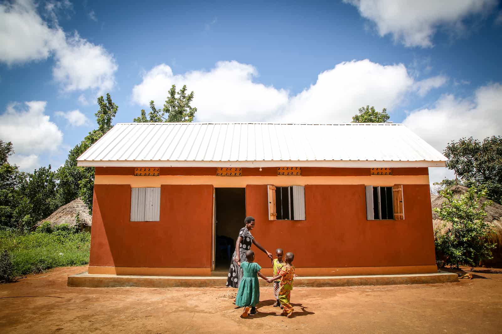 A mother and three children dance in a circle in front of a home with a metal roof.