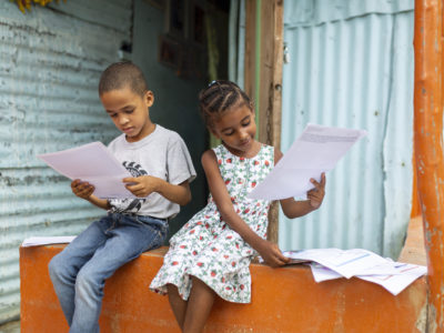 Two children sit outside on a porch, reading letters.