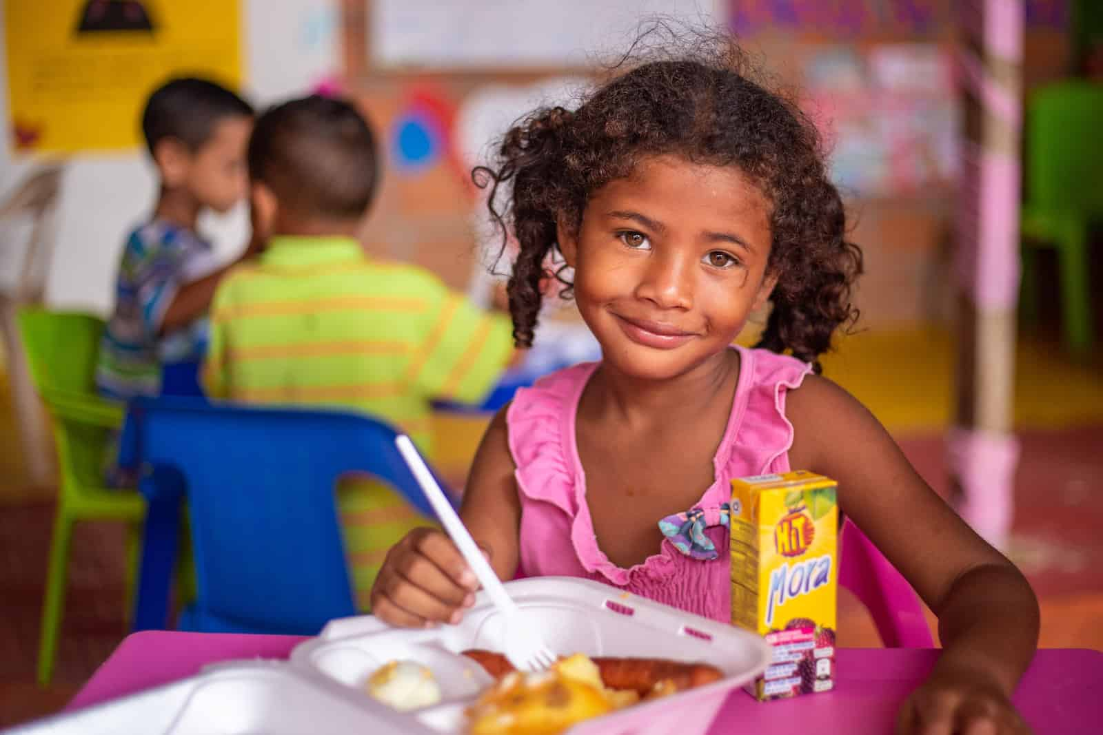 A young girl sits in front of a plate of food.