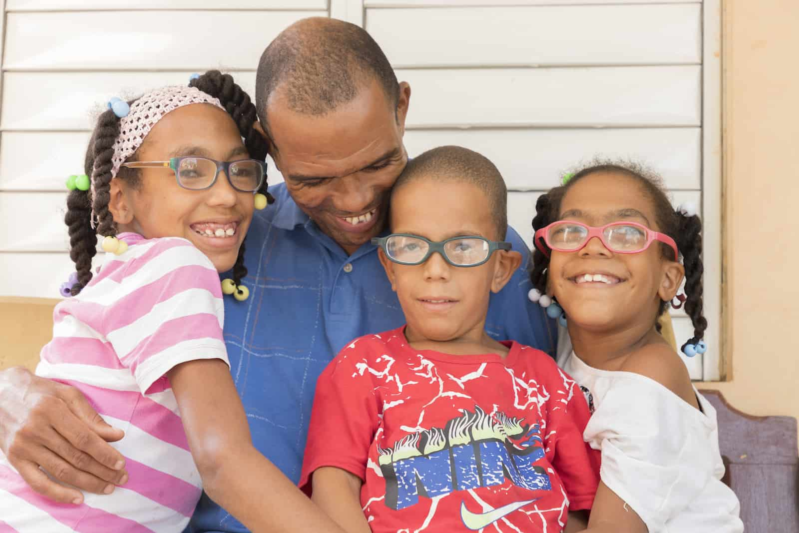 A man sits, hugging three children with glasses.