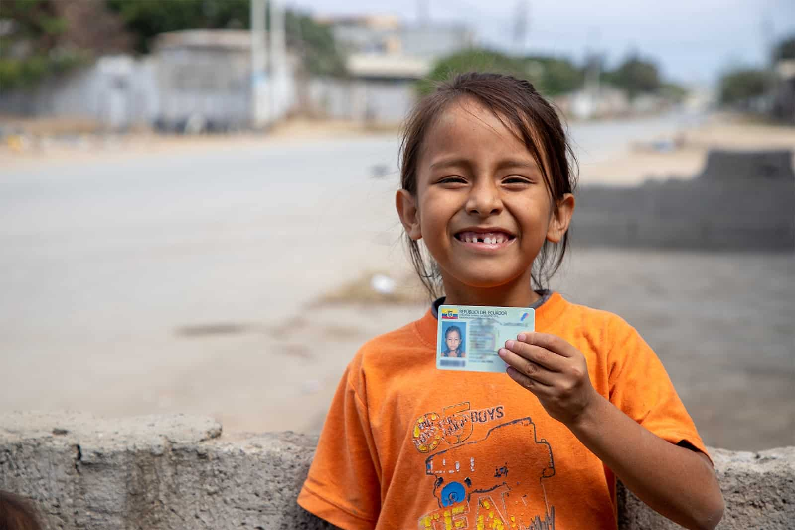 A girl in an orange shirt holds up an identification card.