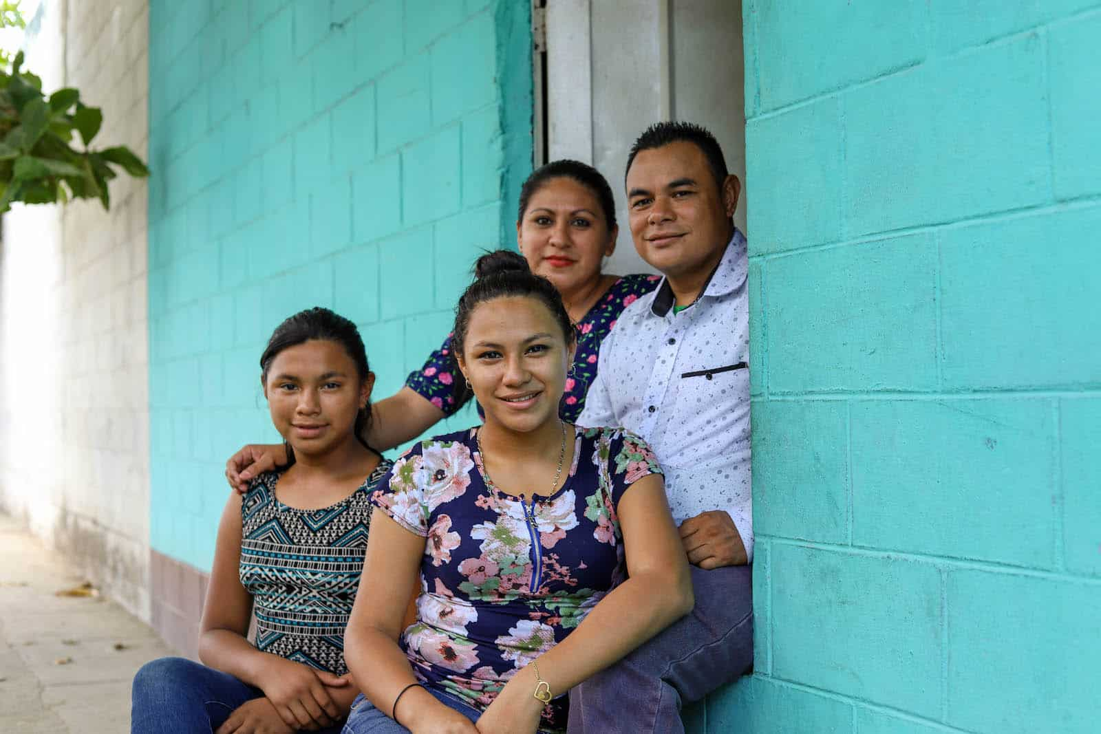 A family of four sits on the doorstep of a turquoise painted home.