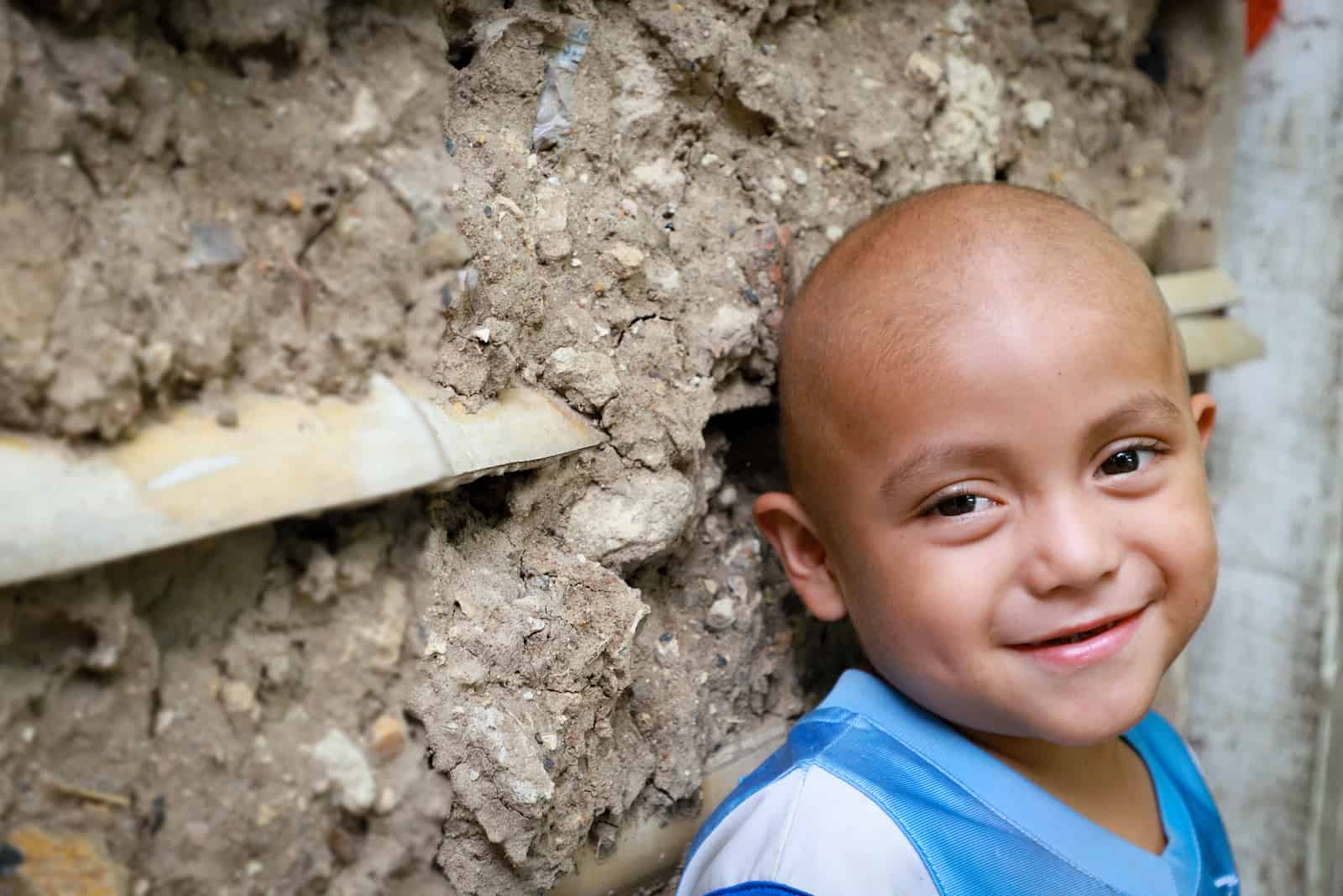 A young boy with no hair leans against a mud wall, smiling.
