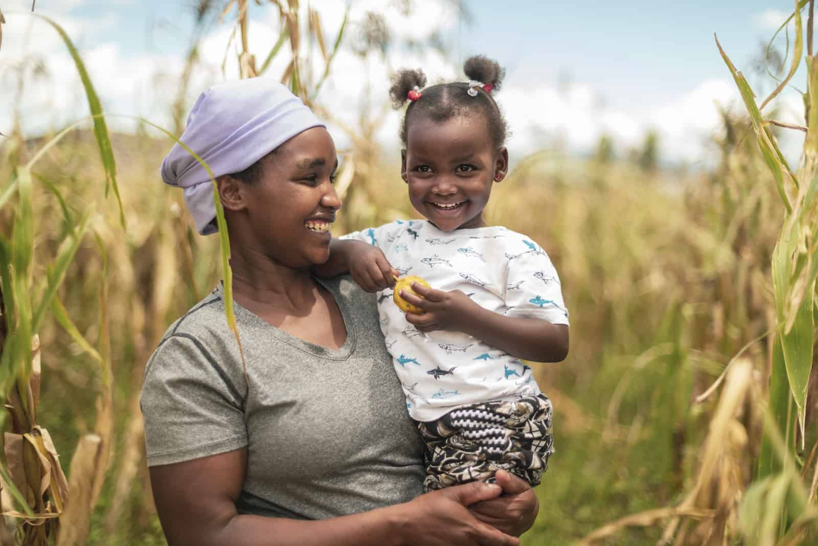 A woman in a cornfield holds a toddler.