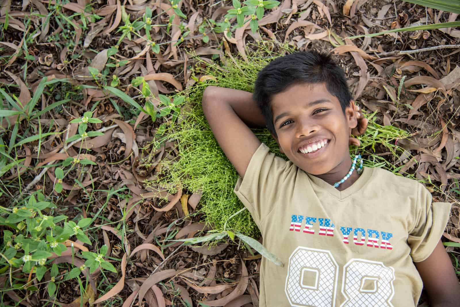 A boy in a tan shirt lays in the grass on the ground, smiling.