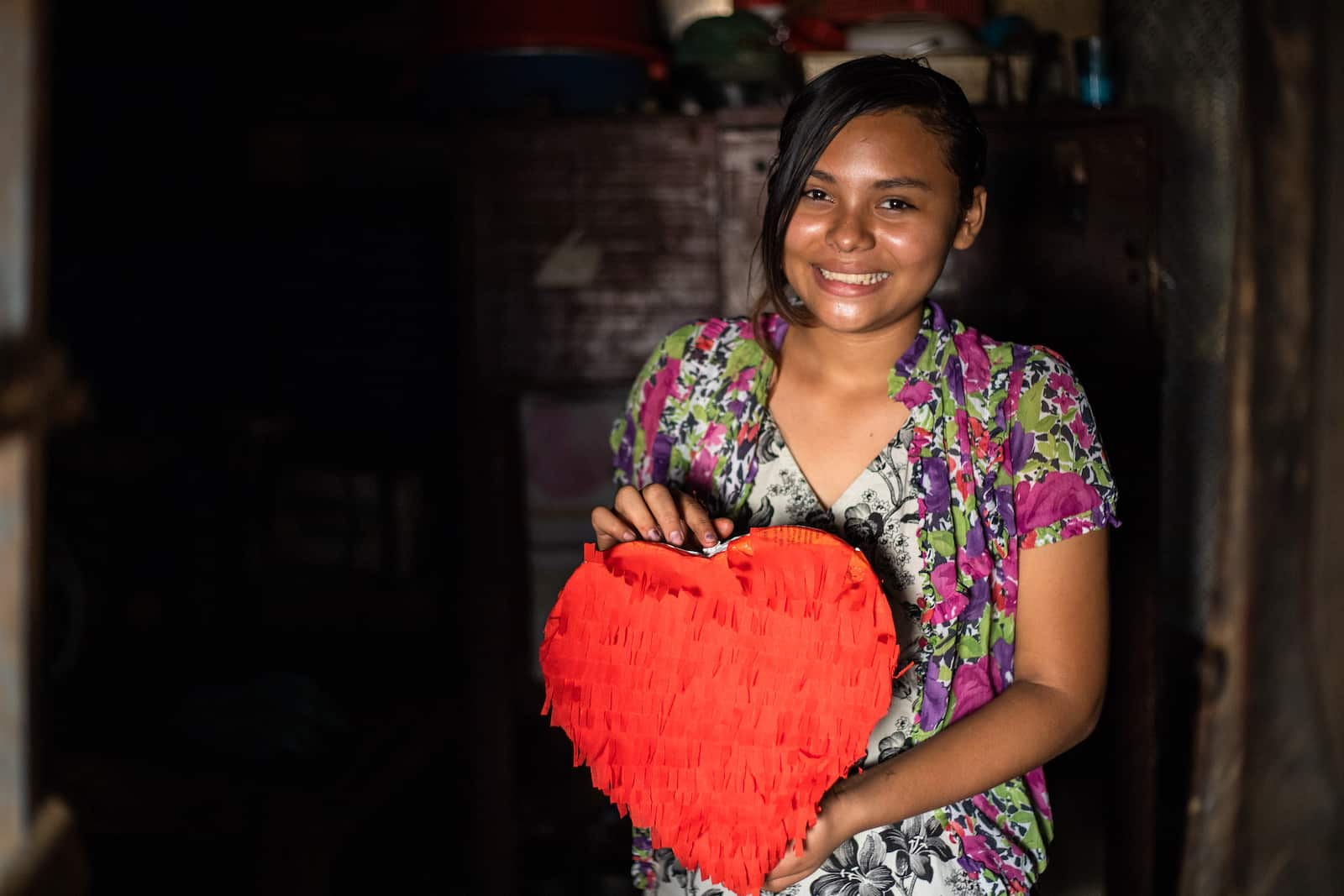 A girl in a floral shirt holds a red heart pinata.