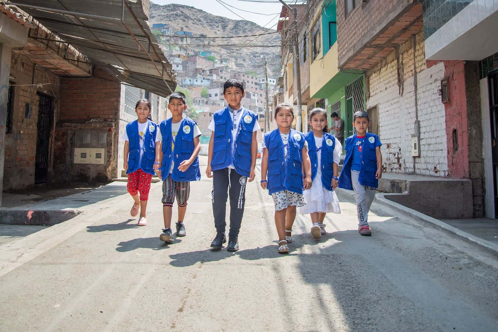 A group of children in blue vests walk down a street in Peru.