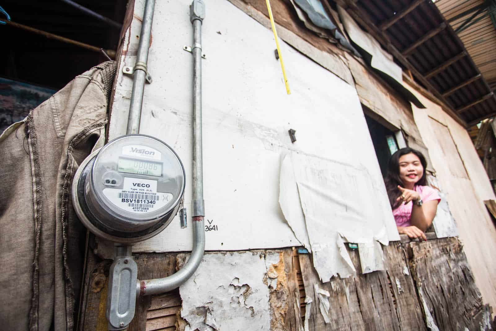 A girls leans out of a window of a makeshift home, pointing at an electrical meter.