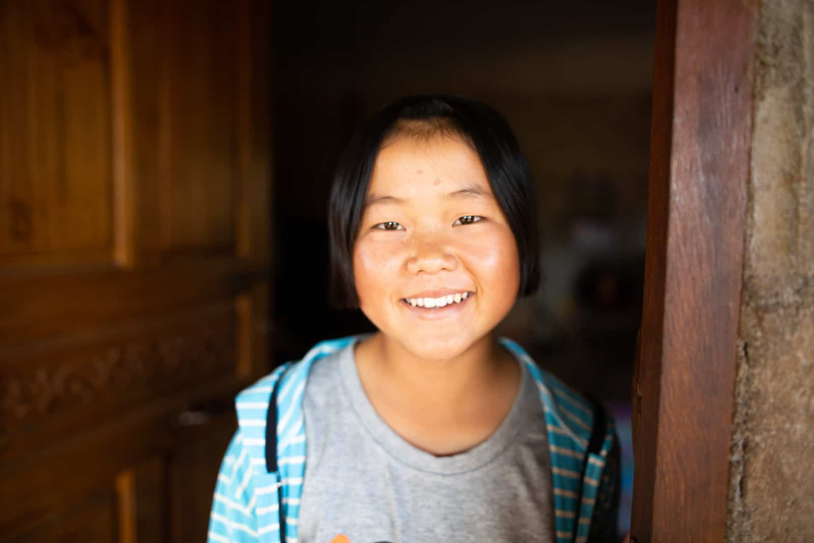 A girl in a grey shirt stands in the doorway of a home, smiling.