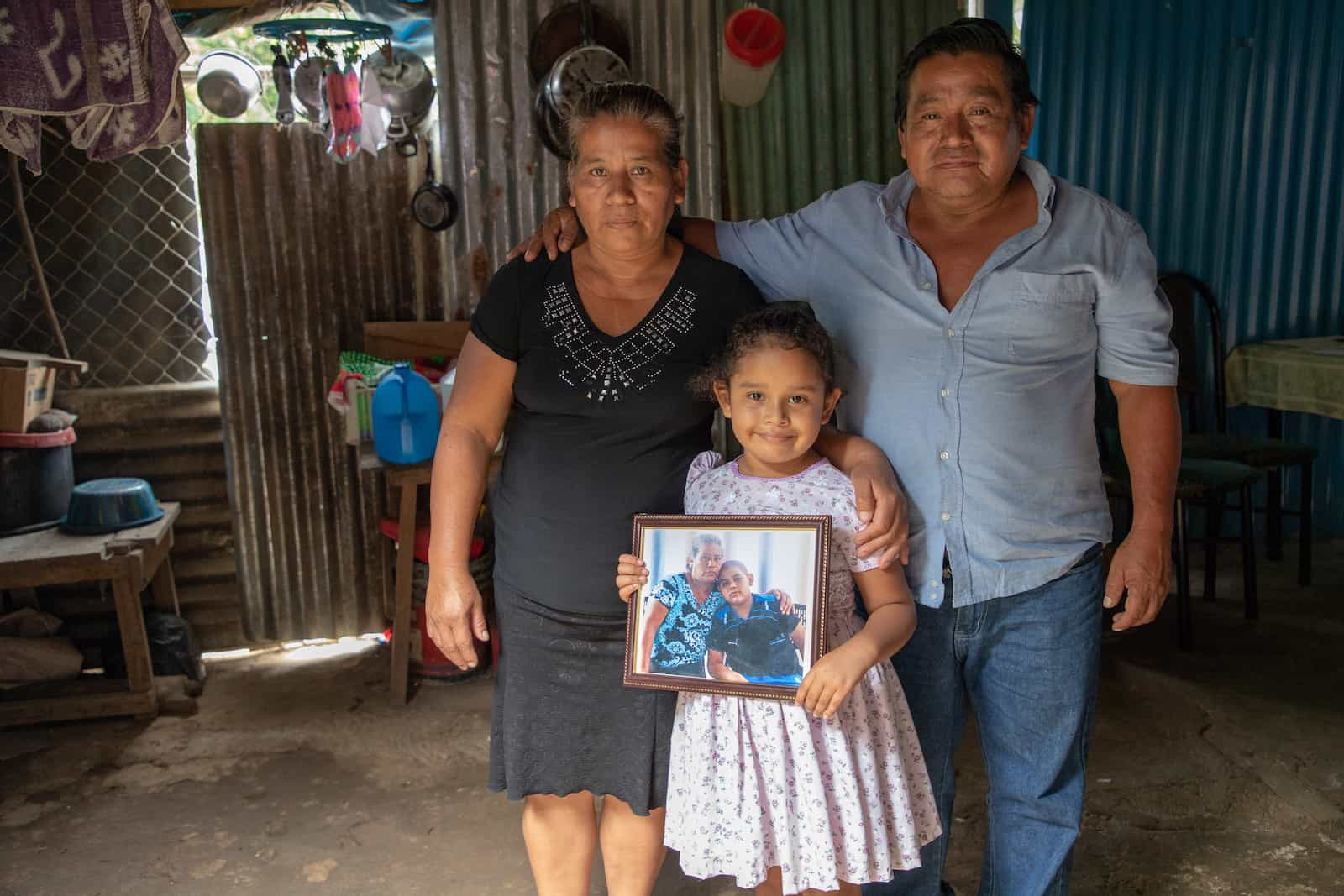 A woman and a man stand behind a little girl holding a picture of a young boy and his grandma.