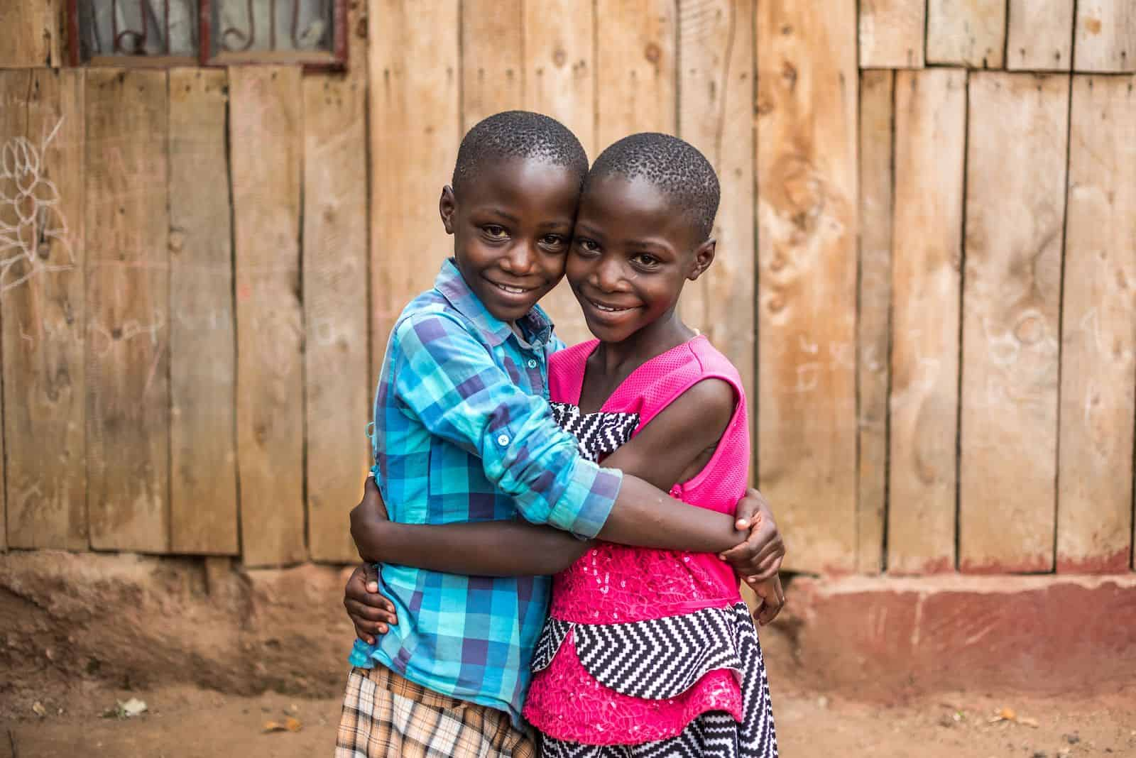 How to Help Kids in Need: Two girls hug each other, standing in front of a wooden home
