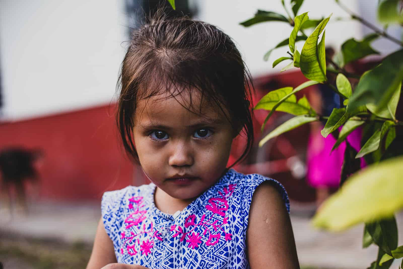 How to Help Kids in Need: A girl wearing a blue dress looks at the camera with a serious look on her face.