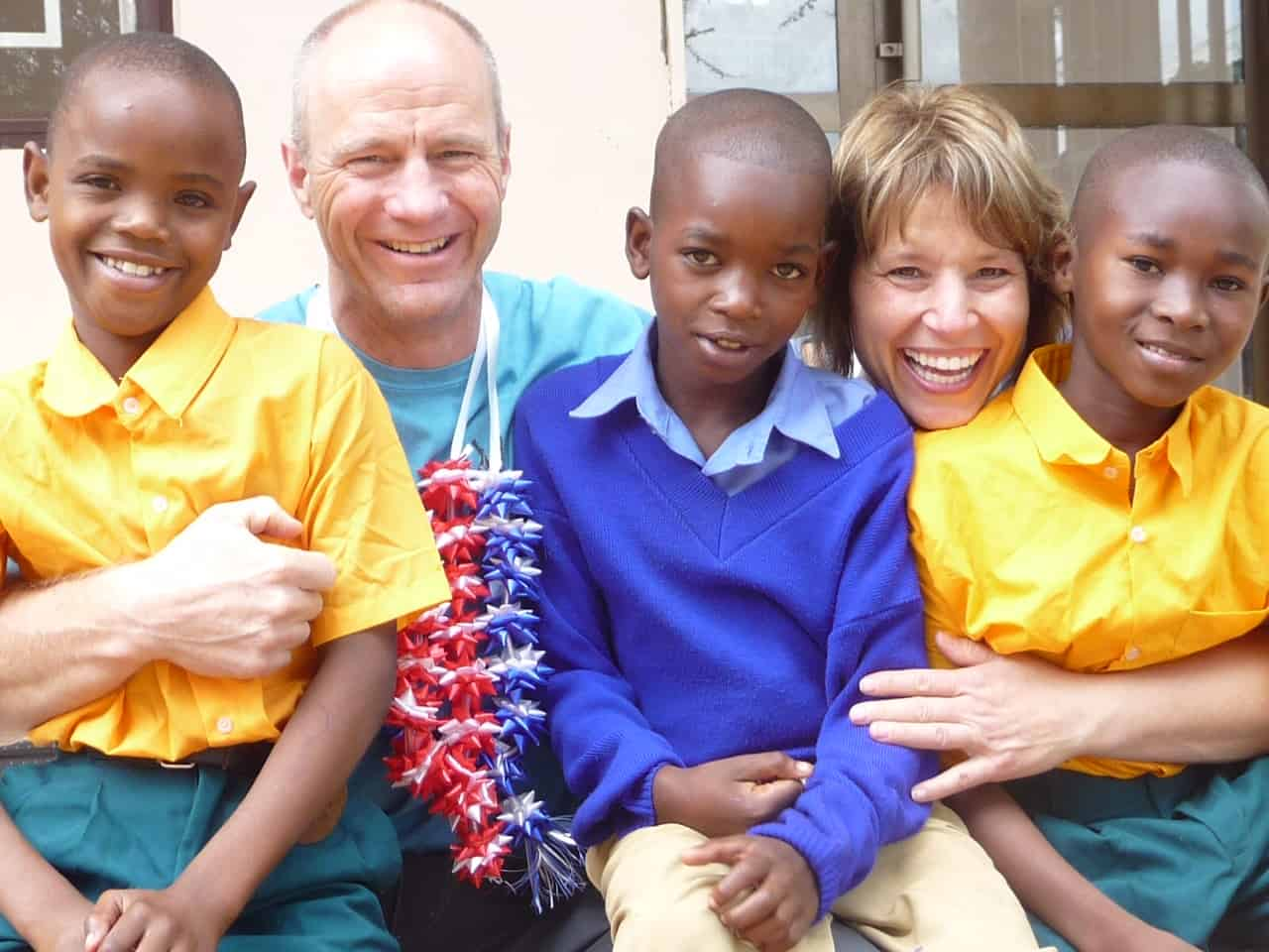 A man and woman hug three children in school uniforms
