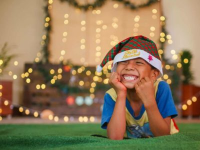 A boy wearing a Santa cap lays on the ground with his face resting in his hands, smiling.
