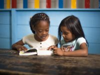 Year of the Bible: Two girls read the Bible together.