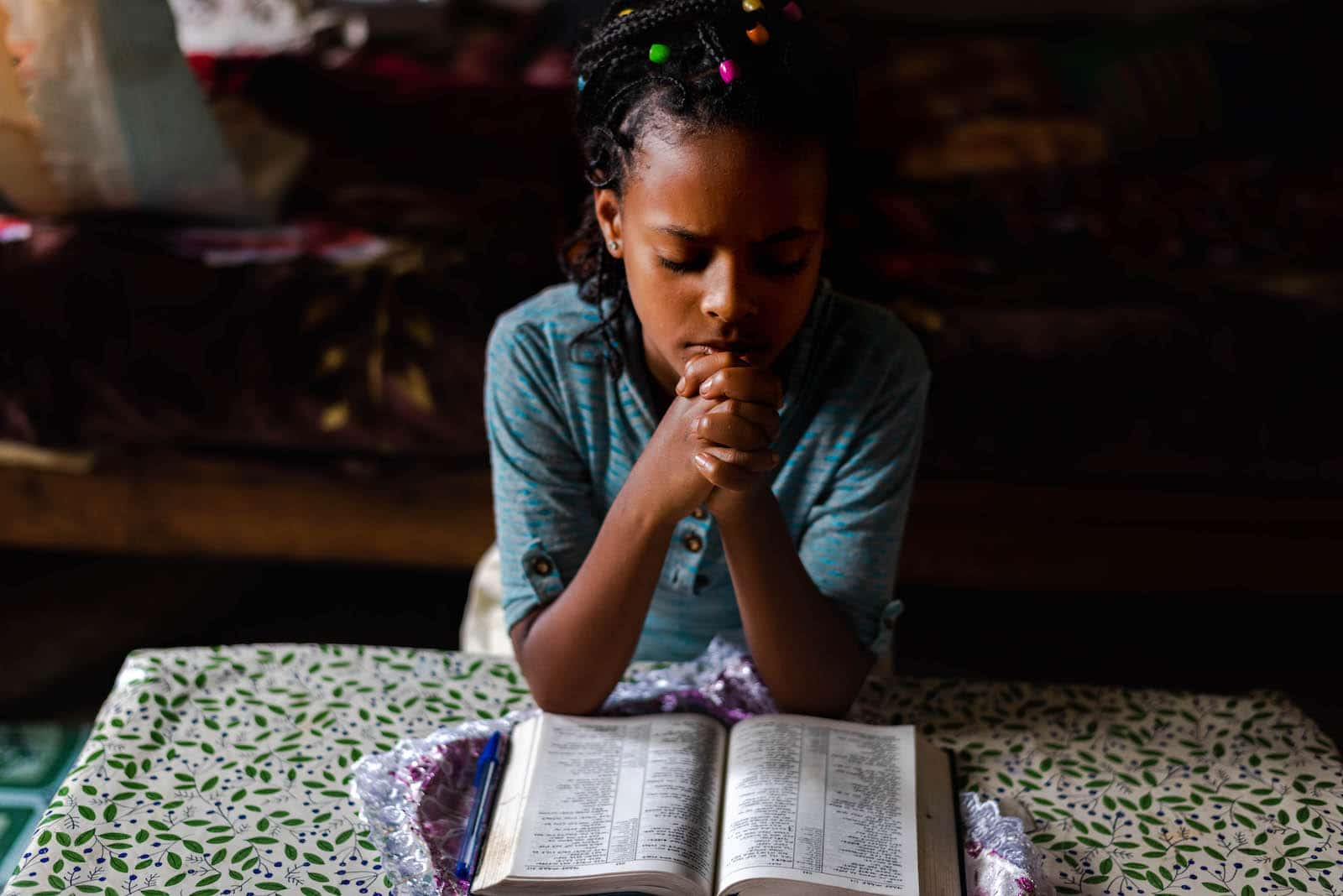 A girl leans on a bed, praying over a Bible.