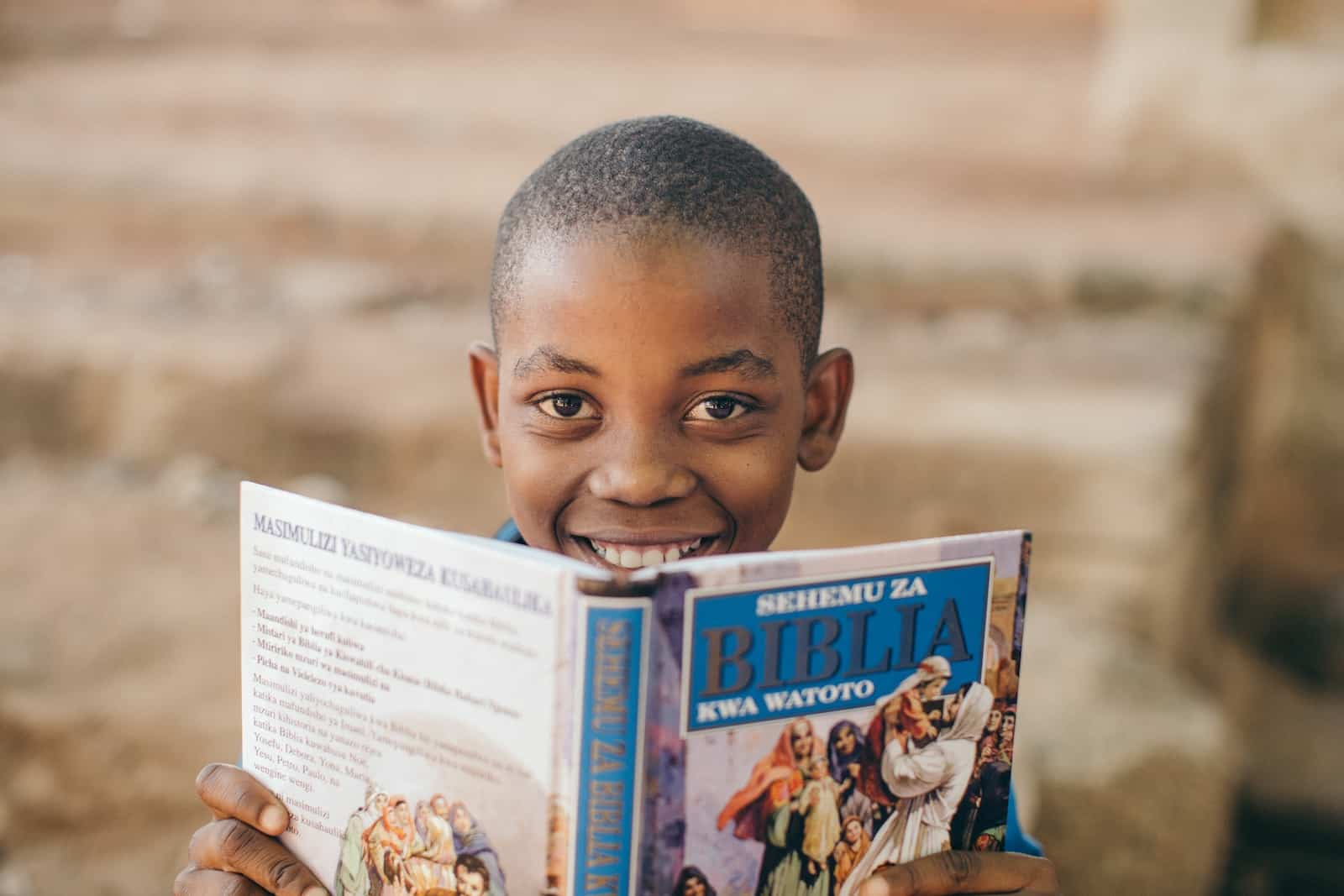 A boy holds an open Bible in front of his face, smiling.