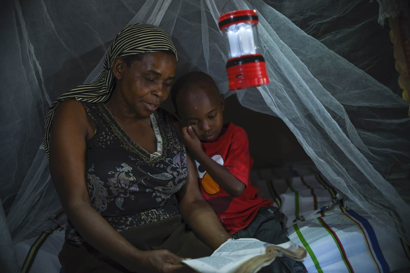 A woman and a boy sit on a bed with a mosquito net and lantern hanging over it, reading the Bible.