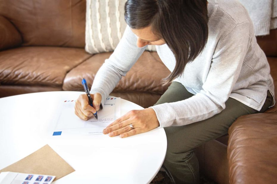 A woman sits at a table, writing a letter.