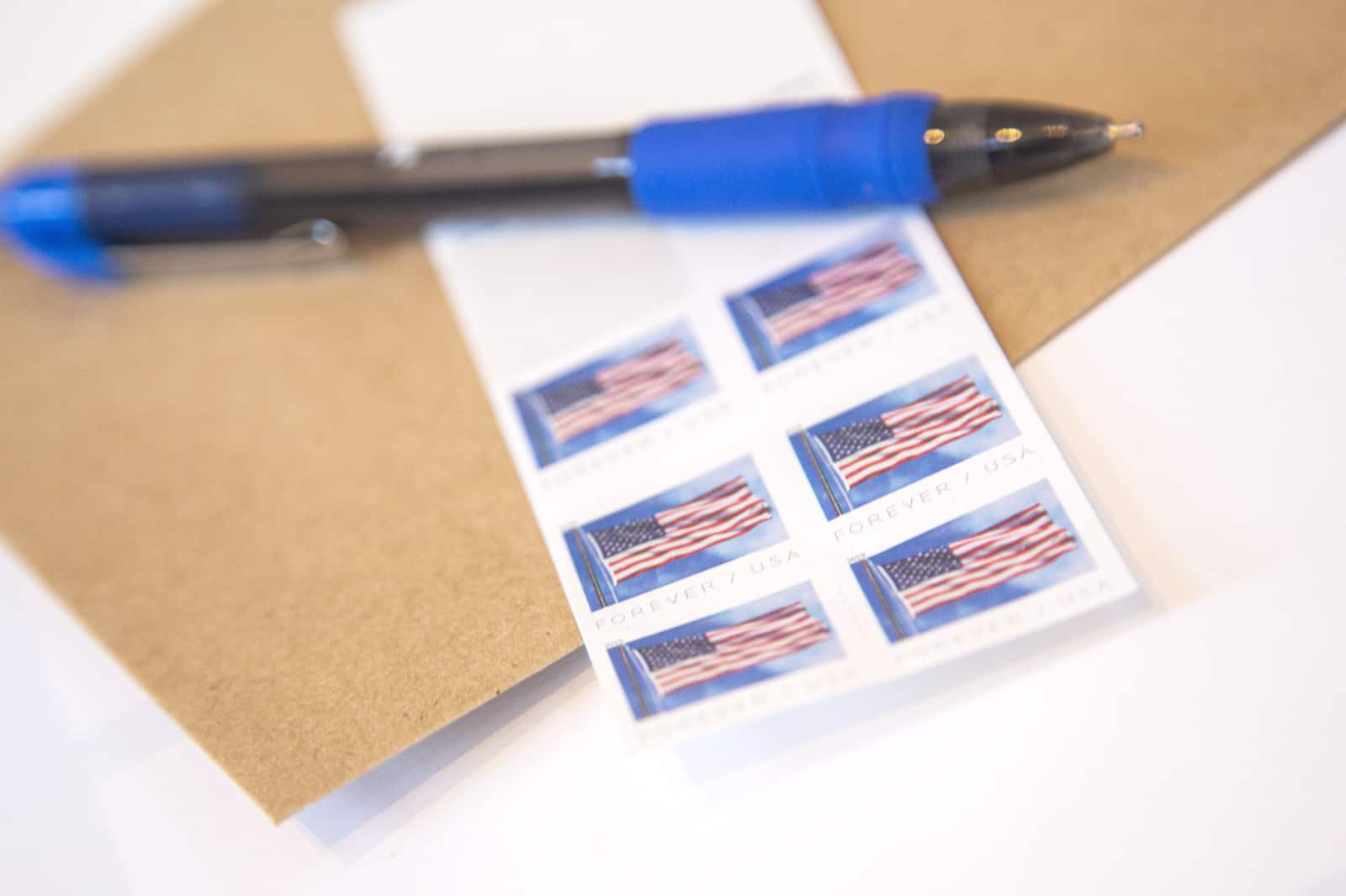 A pen sits atop postage stamps and an envelope.